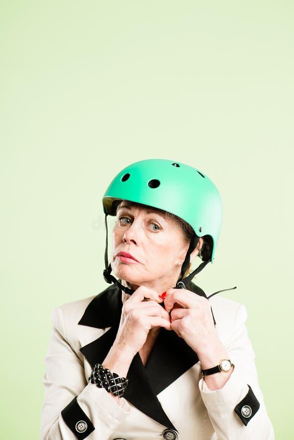 Rolig kvinna som ha på sig verklig cykla rosa bakgrund för hjälmstående royaltyfri bild