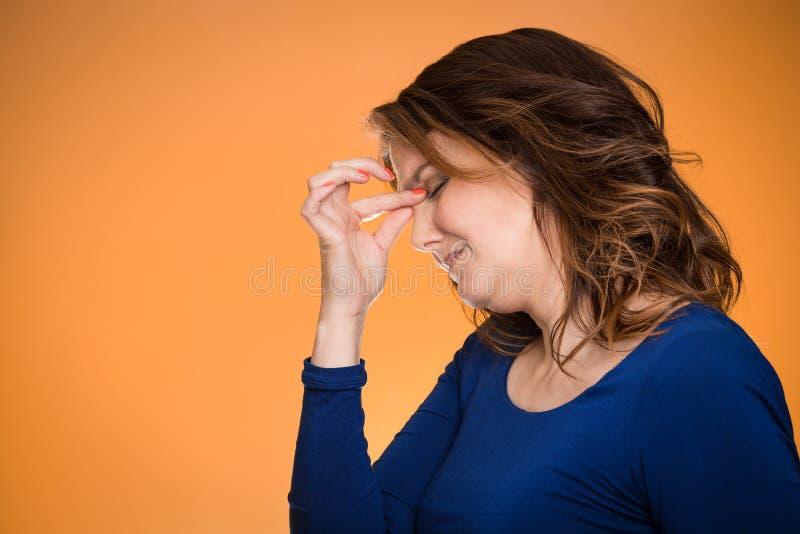 Åldrig kvinna för stressad hemmafrumitt med huvudvärk arkivbilder