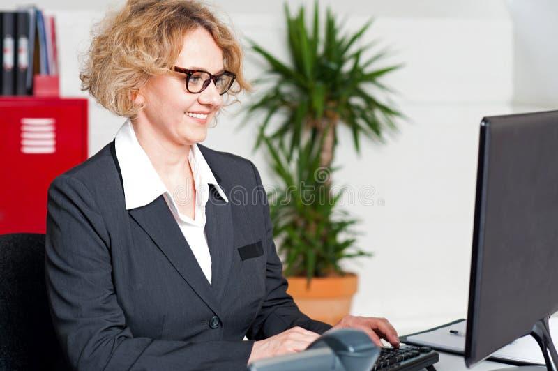 Åldrig kvinna i glasögon som fungerar på datoren royaltyfri fotografi