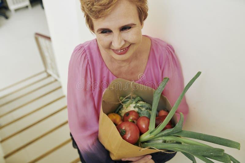 Åldrig kvinna med påsen av livsmedel arkivfoton