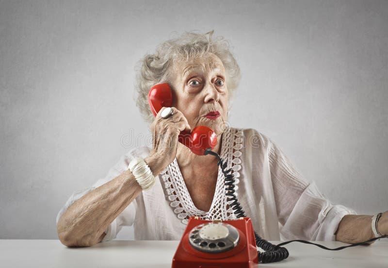 Åldrig kvinna som talar på en tappningtelefon arkivbilder