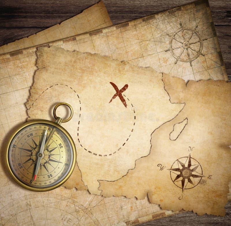 Åldrig mässingsnautisk kompass på tabellen med gamla översikter royaltyfri illustrationer