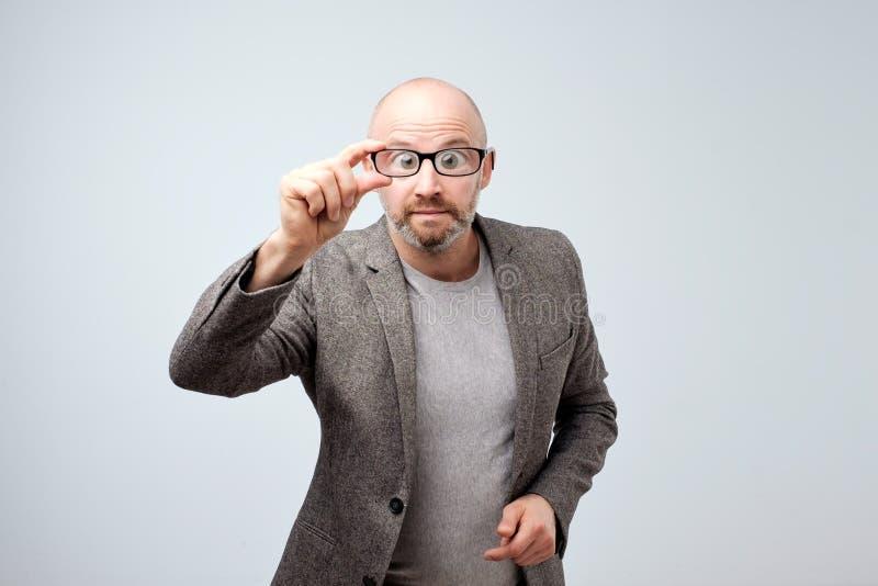 Åldrig man för rolig mitt som ser till och med exponeringsglas Hans ögon är stora royaltyfria foton