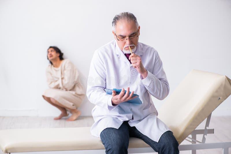 Åldrig manlig doktorspsykiater som undersöker den unga patienten arkivfoto