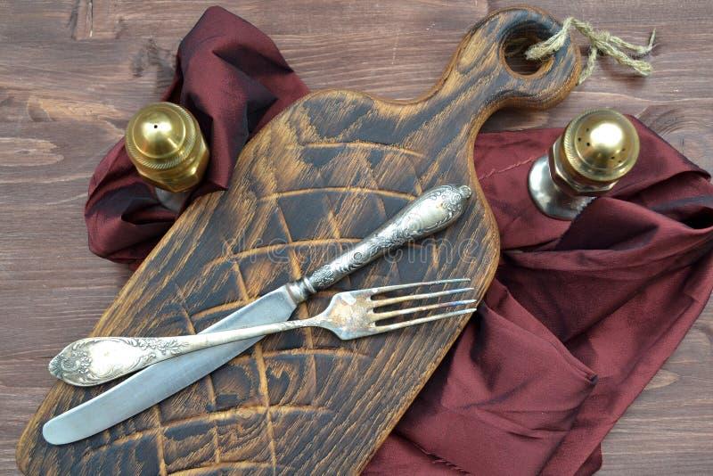 Åldrig skärbräda med antikvitetsilverpepperboxen och gaffel på trätabellen Begreppet av sunt bantar arkivfoto