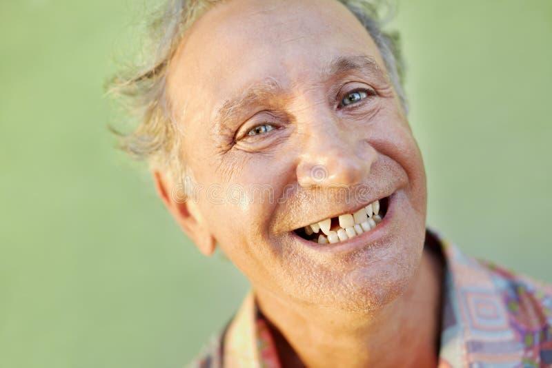 Åldrig tandlös man som ler på kameran arkivbilder