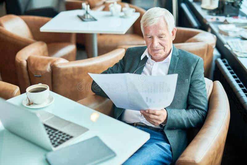 Åldriga affärsmanläsningdokument i kafé fotografering för bildbyråer