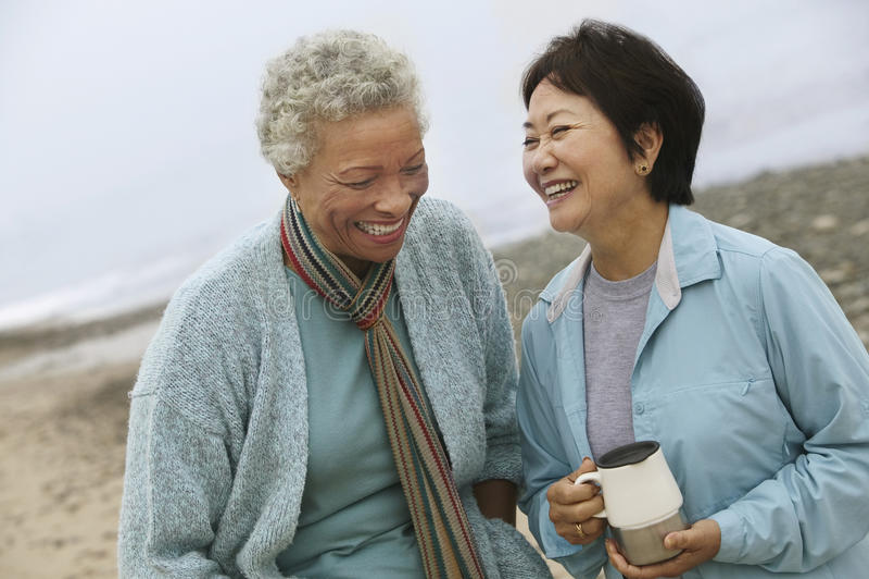 Åldriga kvinnliga vänner för gladlynt mitt på stranden fotografering för bildbyråer