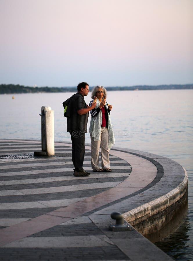 Åldriga par på en promenad som ser solnedgång på Garda sjön i Lazise, royaltyfri bild