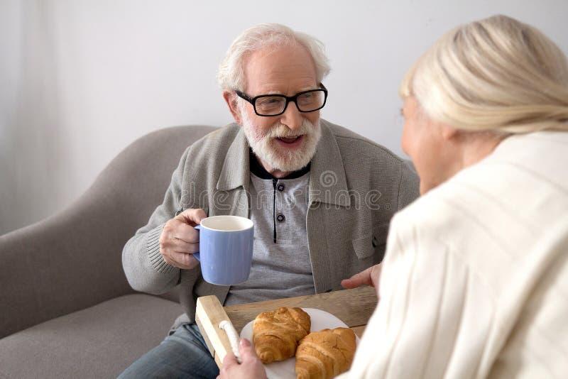 Åldriga par som har kaffe på soffan fotografering för bildbyråer