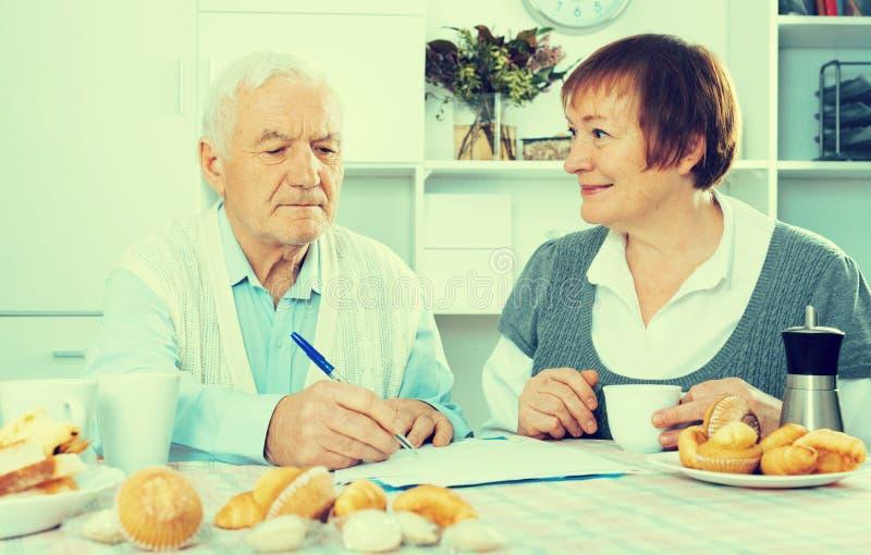 Åldriga par som kämpar till lönräkningar royaltyfri foto
