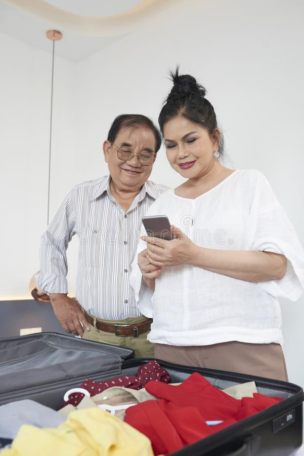 Åldriga par som kontrollerar appen för väderprognos fotografering för bildbyråer
