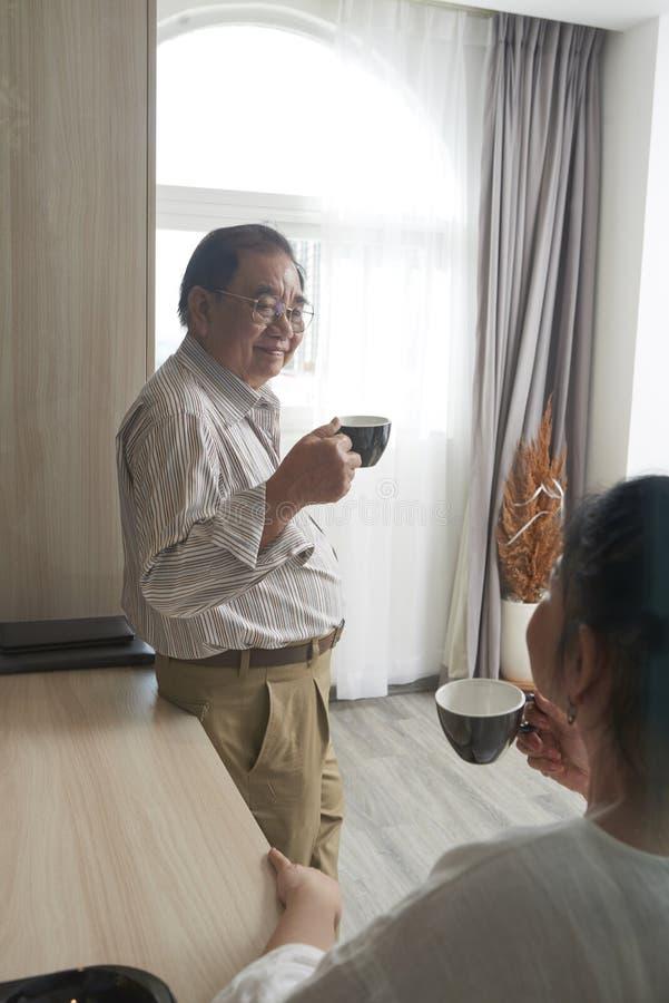 Åldriga par som tycker om te och konversation royaltyfri fotografi
