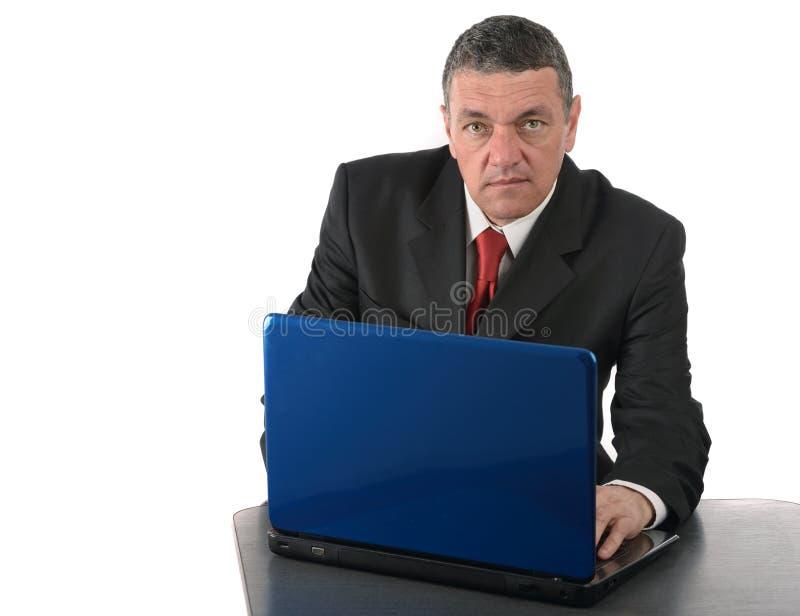 Åldrigt affärsmansammanträde på skrivbordet med en bärbar dator som isoleras på vit arkivfoto