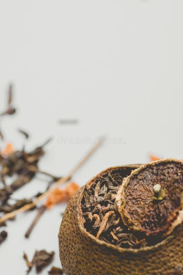 Åldrigt jäst svart kinesPuer te i tangerinPeel med locket Vit bakgrund Sund dryck för asiatisk kokkonst close upp fotografering för bildbyråer