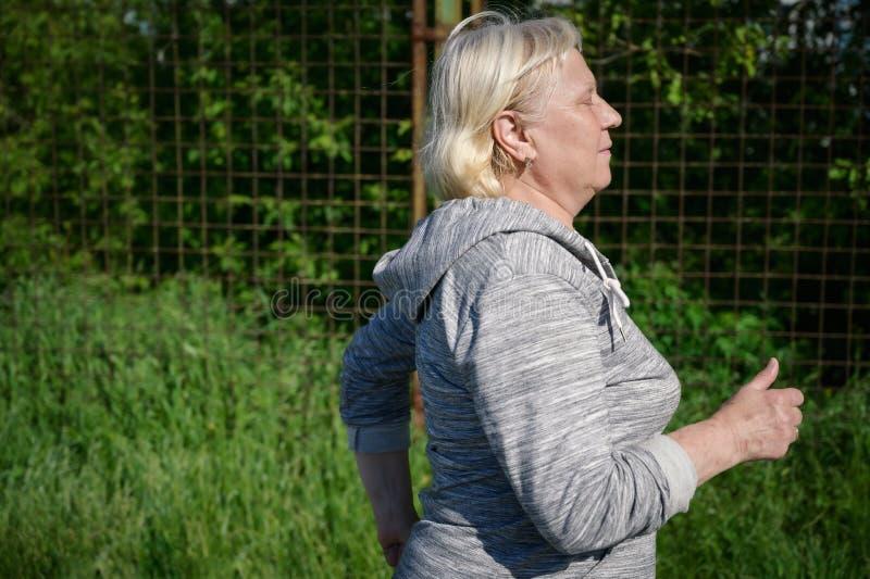 Åldrigt jogga för kvinna arkivfoto