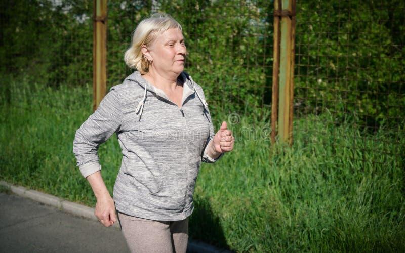 Åldrigt jogga för kvinna fotografering för bildbyråer