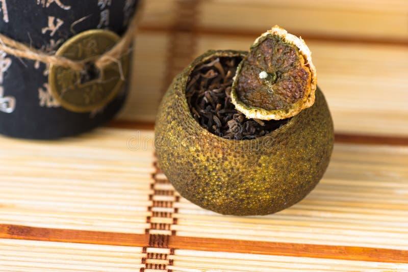 Åldrigt pu-erh te i en torr tangerinpeel på ett mattt sugrör för kinesisk stil, selektiv fokus royaltyfria foton
