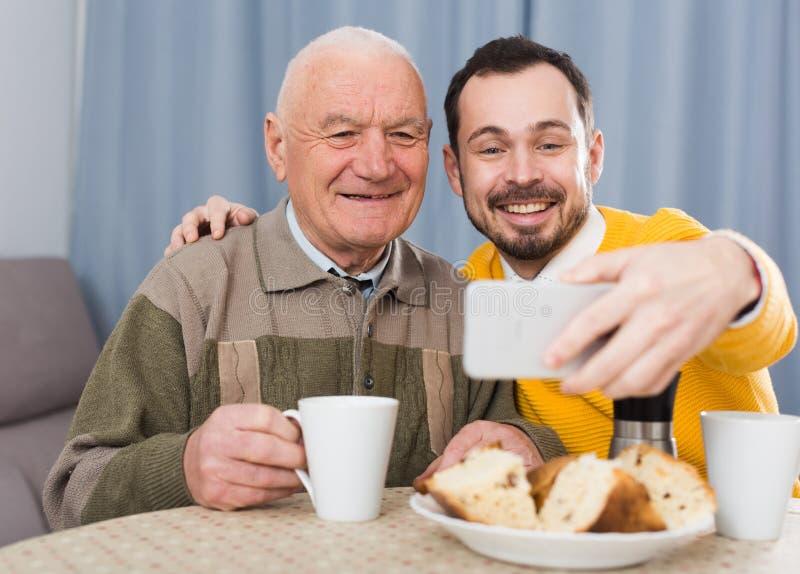 Åldring fader och son som gör selfie fotografering för bildbyråer