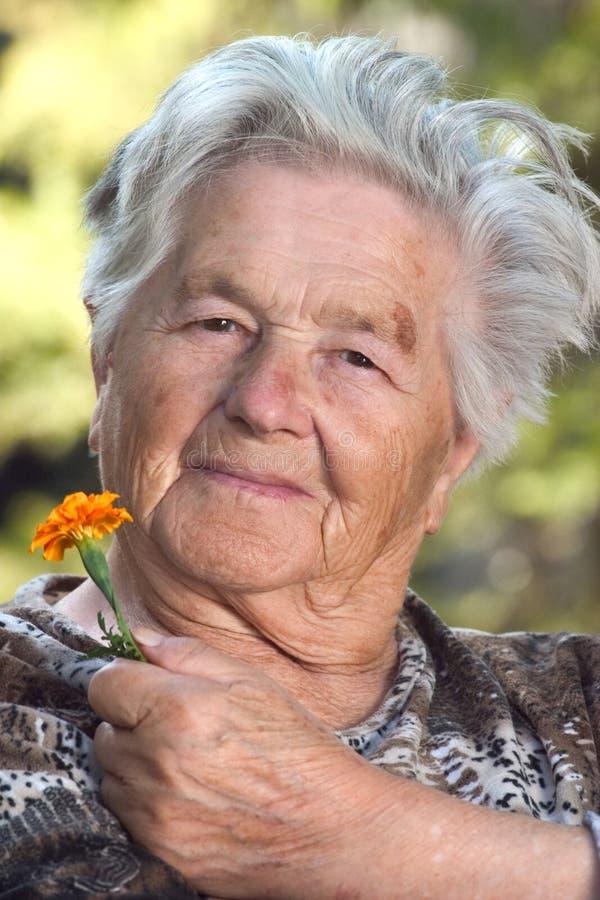 åldringblommakvinna royaltyfria foton