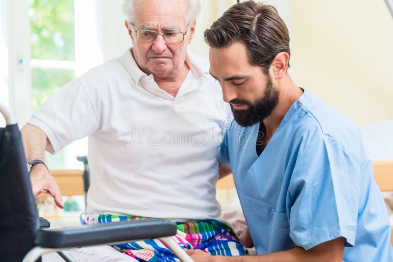 Åldringen att bry sig sjuksköterskaportionpensionären från säng till hjulstol royaltyfri bild