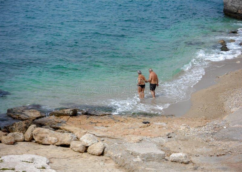 Åldringen kopplar ihop att gå för att simma på en liten strand i den Piraeus staden Grekland arkivbild