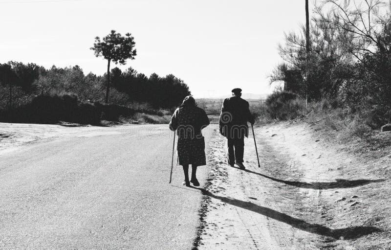 Åldringen kopplar ihop att gå på vägen, morföräldrar som utomhus går med rottingen arkivbild