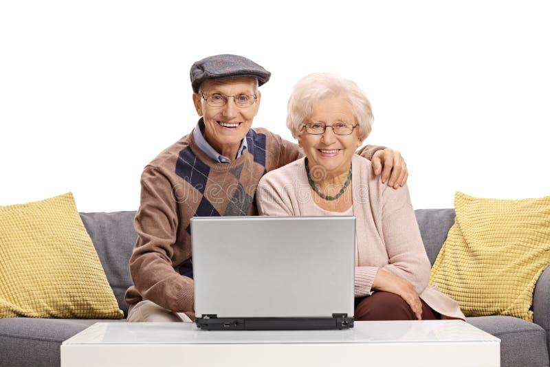 Åldringen kopplar ihop med ett bärbar datorsammanträde på en soffa arkivfoto
