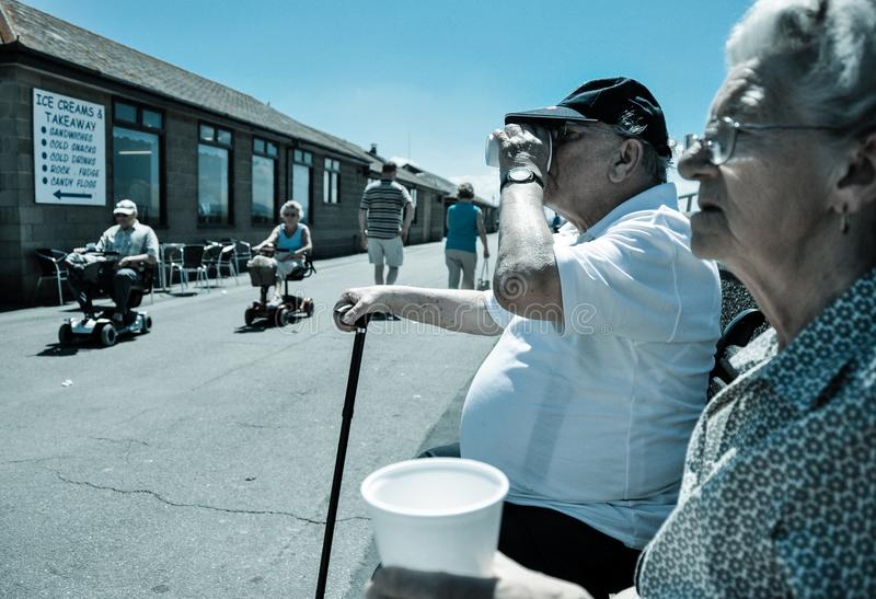 Åldringen kopplar ihop smuttte, som pensionärer kryssar omkring förbi på motoriserade vagnar arkivbild