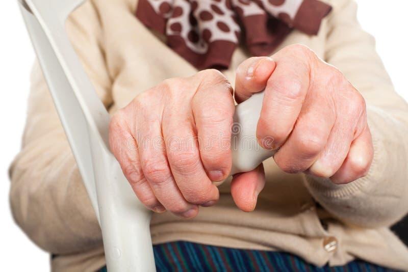 Åldringhänder som rymmer en krycka royaltyfri foto