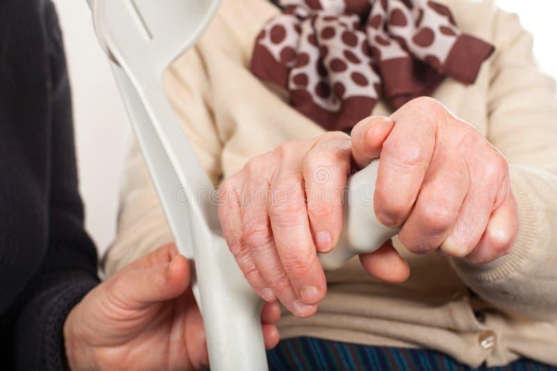 Åldringhänder som rymmer en krycka royaltyfria foton