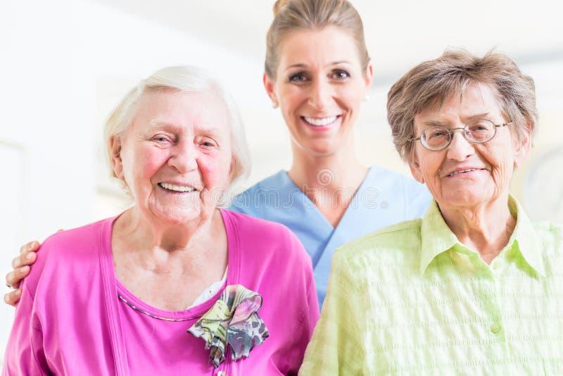 Åldringomsorgsjuksköterska med två höga kvinnor arkivbild