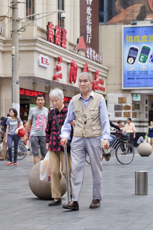 Åldringpar går i centret, Shanghai, Kina arkivfoton