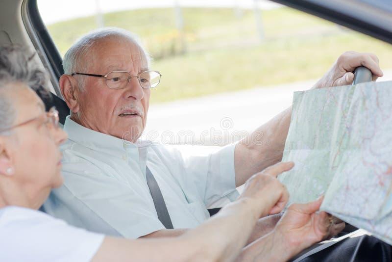 Åldringpar som kör frun som pekar till översikten royaltyfri fotografi
