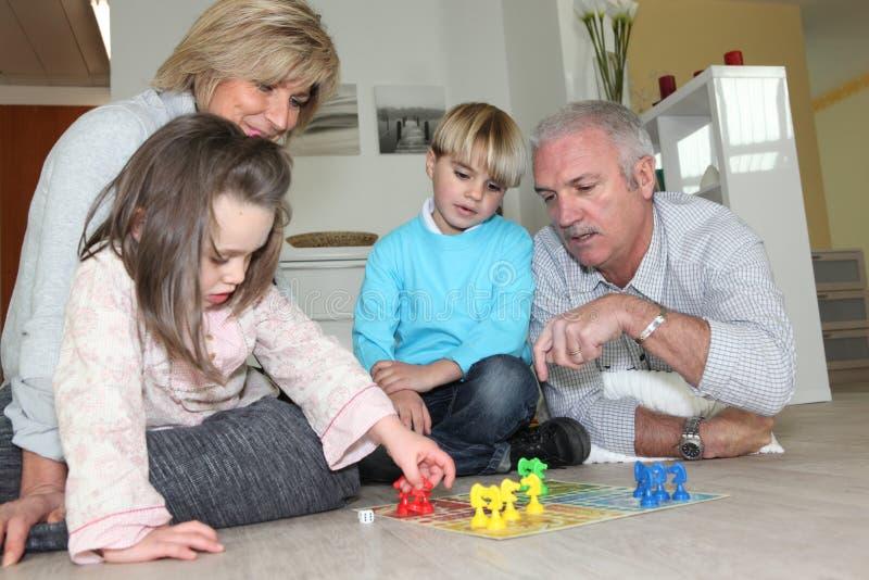 Åldringpar som spelar med barnbarn fotografering för bildbyråer