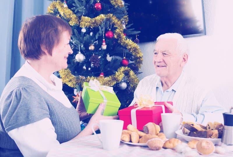 Åldringparet ger julgåvor fotografering för bildbyråer
