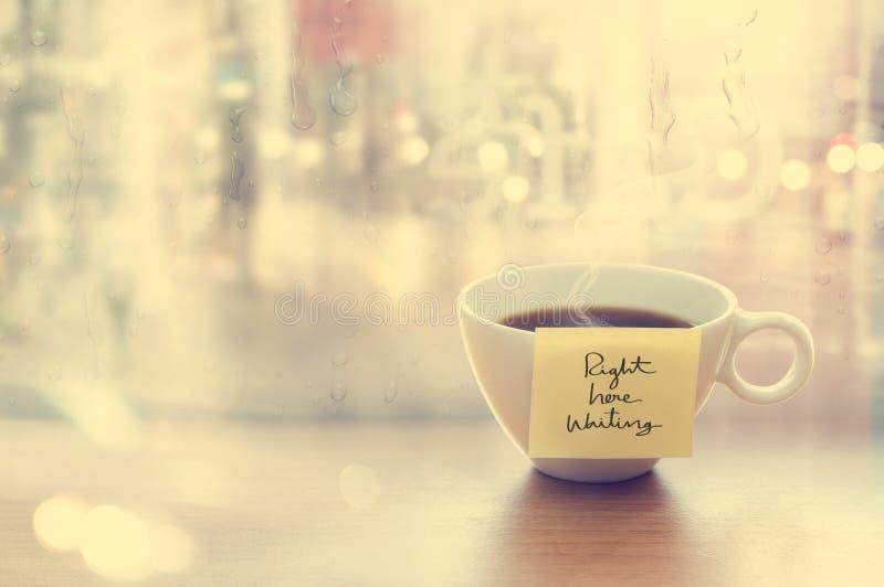 Ånga kaffekoppen med sinnesrörelsemeddelandekoppen i coffee shop, framdel av spegel- och regndroppefönstret, tappningfärg och det royaltyfri bild