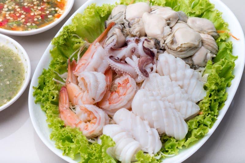 Ångad räka och tioarmad bläckfisk och rå ostron arkivfoton