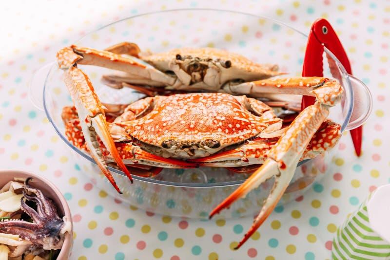 Ångade krabbor för ny blomma i exponeringsglasbunke med den röda krabbasmällaren royaltyfria bilder