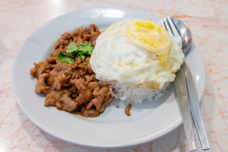 Ångade ris som överträffades med ett stekt ägg med stekt under omrörning griskött med vitlök, satte i en maträtt royaltyfria foton