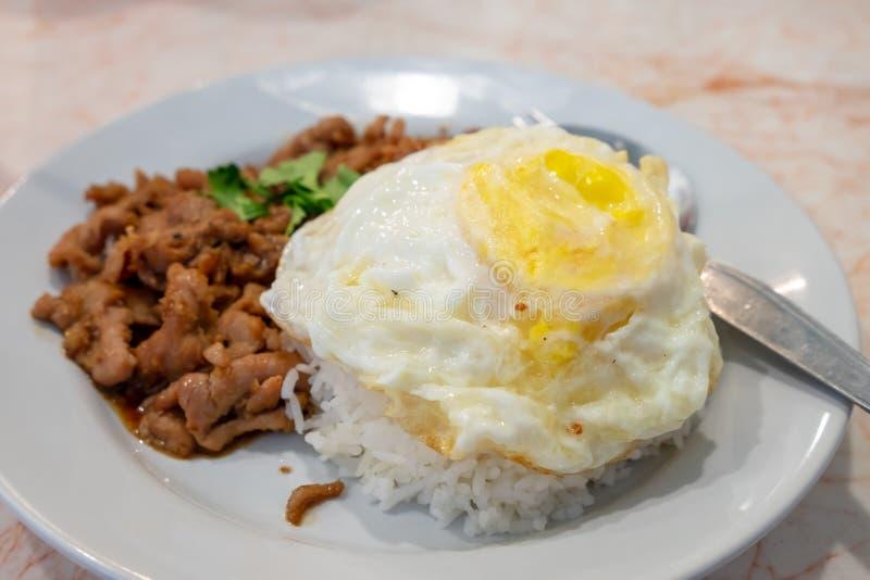Ångade ris som överträffades med ett stekt ägg med stekt under omrörning griskött med vitlök, satte i en maträtt arkivbilder