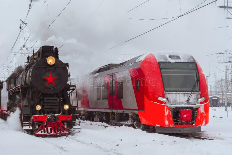 Ångalokomotiv och modern multipel-enhet drevställning som är närliggande på stationen royaltyfri foto