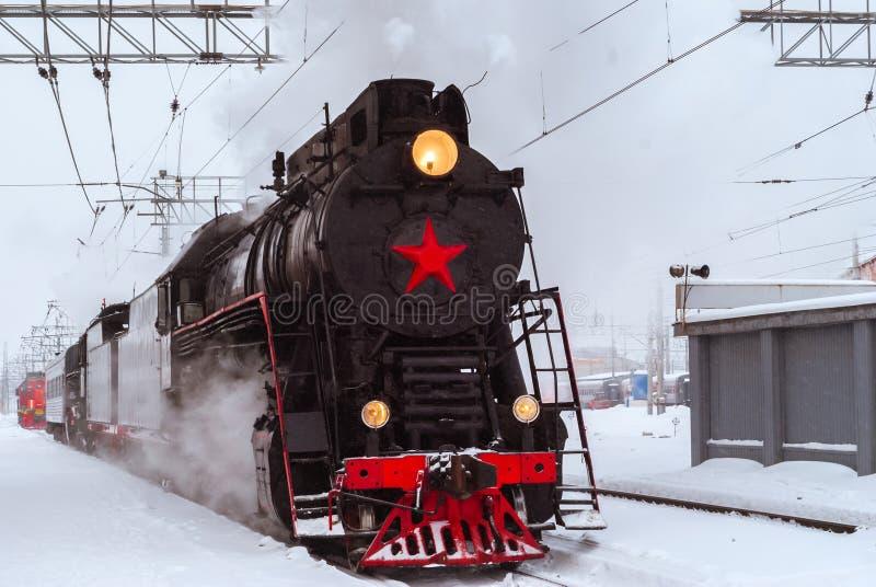 Ångalokomotiv på stationen i vinter arkivbild