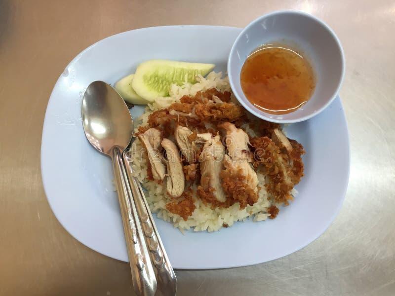 Ångat fegt med den stekte ris och gurkan med en kopp av den söta sås- och skedgaffeln i den vita maträtten royaltyfria bilder
