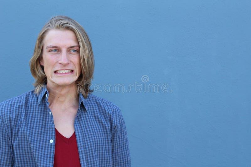 Ånger förorättar att göra Enfaldig ung man för Closeupstående och att ha duh ett ögonblick som isoleras på blå bakgrund Negativ m royaltyfri fotografi