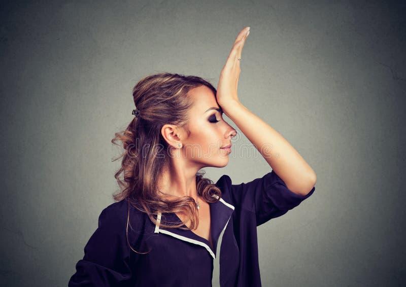 Ånger förorättar att göra Ledsen kvinna som smäller handen på huvudet som har duh ögonblick som isoleras på grå bakgrund royaltyfri fotografi