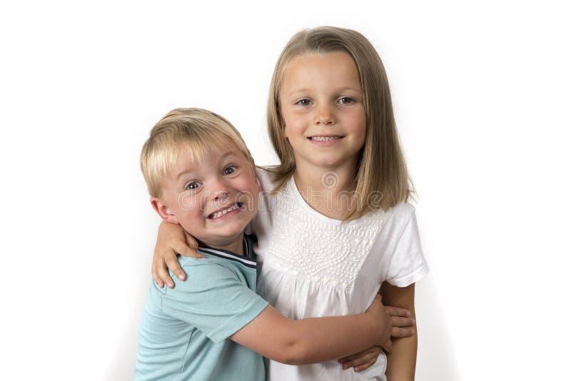 7 år gammal förtjusande blond lycklig flicka som poserar med hennes lilla 3 år gammal broder som ler gladlynt som isoleras på vit arkivfoton