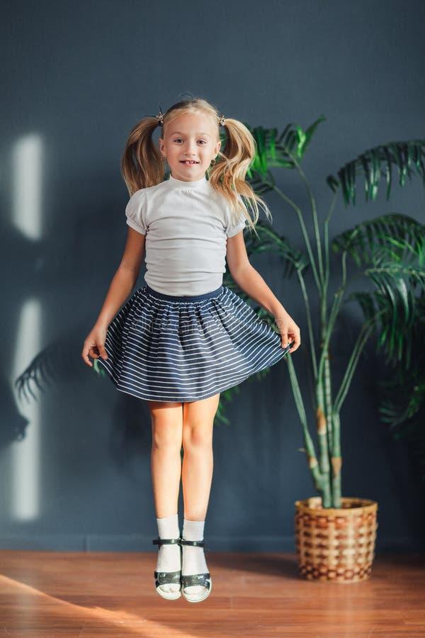 8 år gammal härlig liten blond flicka med hår som samlas i svansar, den vita t-skjortan, vita sockor och grå kjol som hoppar i et royaltyfri bild