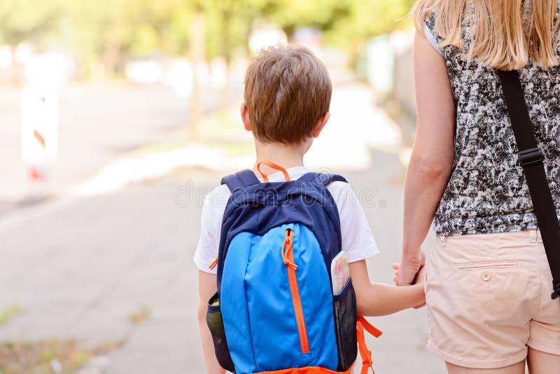 7 år gammal pojke som går till skolan med hans moder fotografering för bildbyråer