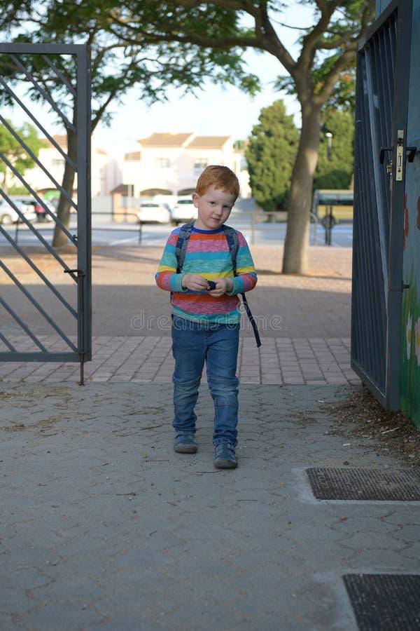 5 år gammal redheaded pojke som skriver in skolan Han är lite ledsen royaltyfri foto
